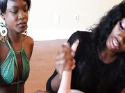 Two ebony sluts jerk off big throbbing knob